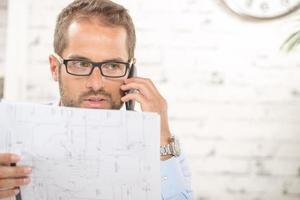 jovem com óculos lê um plano e telefone foto