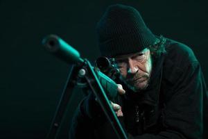 franco-atirador com barba de preto segurando a arma. tiro do estúdio.