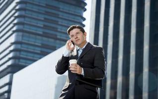 empresário atraente de terno falando no celular feliz ao ar livre foto