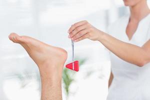 fisioterapeuta usando martelo de reflexo foto