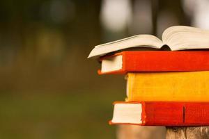 pilha de livro e livro de capa dura aberto no pano de fundo desfocado.
