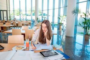 menina estudando na cantina da universidade com fresco e bolo foto