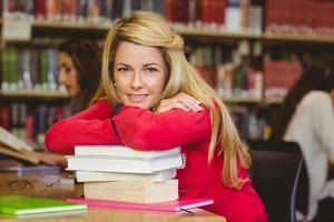 estudante maduro sorridente, inclinando-se sobre uma pilha de livros foto