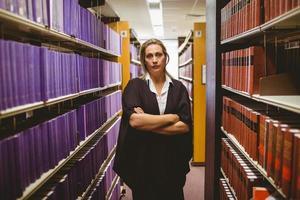 advogado carrancudo em pé entre prateleiras com os braços cruzados foto