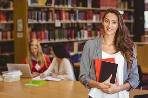 bonita estudante segurando livros com colegas atrás dela foto