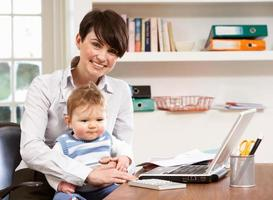 mulher com bebê trabalhando em casa usando laptop foto
