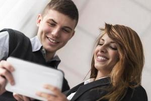 jovem homem e mulher usando um dispositivo tablet foto