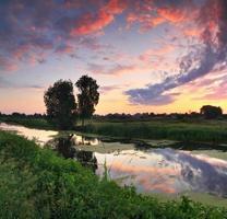 amanhecer na margem do rio foto