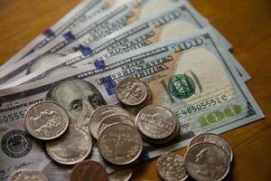 moedas e notas de dólares.