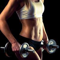 garota fitness - mulher jovem e atraente malhar com halteres