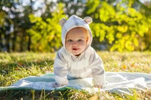 menino bonito caucasiano no parque olha para a câmera foto