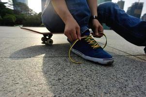 skatista amarrar cadarço no skate park foto