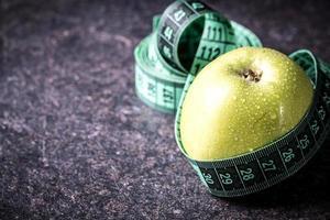 miolo de maçã verde e fita métrica. conceito de dieta foto
