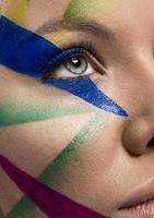close-up do rosto de mulher com maquiagem multicolor