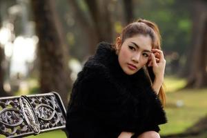 bela asiática de vestido preto, posando no parque foto