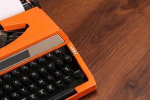 máquina de escrever vintage laranja na madeira foto