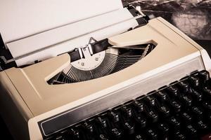 velha máquina de escrever com papel foto