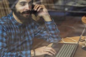 homem jovem hippie trabalhando no laptop na cafeteria foto