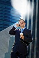 empresário atraente terno falando no telefone móvel oudoors foto