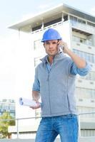 arquiteto usando telefone celular fora do edifício foto