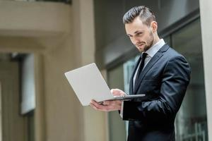 verificação de e-mail. empresário jovem e bem sucedido no laptop foto