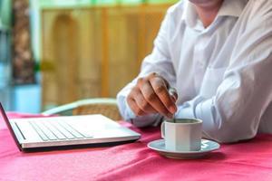 empresário de café da manhã com um laptop em um café foto