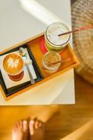 café, matcha gelado com leite e água na mesa de café foto