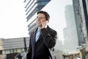 empresário atraente de terno falando no celular ao ar livre foto