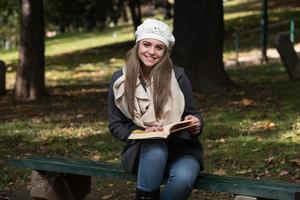 mulher atraente lê o livro na floresta de outono foto