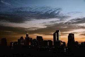 fundo da silhueta da paisagem urbana com céu escuro dramático foto