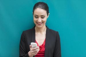 empresária encostado a parede azul, usando um telefone celular.