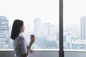 empresária, segurando a xícara de café e olhando pela janela