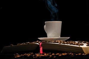 xícara de café expresso com grãos de café com livro velho