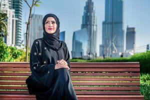 sucesso árabe. empresárias árabes em hijab, sentado no banco foto