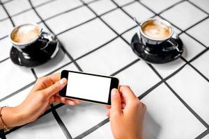 usando o telefone com café no fundo foto