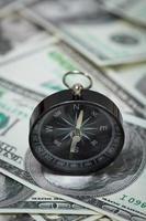 bússola colocada sobre as notas de dólar foto
