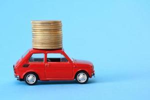 pilha de moedas no carro em miniatura vermelho foto