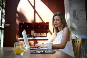 mulher sentada frente computador portátil aberto na cafeteria moderna foto
