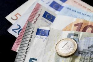 euro dinheiro moeda em um fundo preto foto