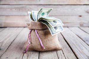 dinheiro em saco de aniagem em fundo de madeira foto