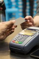 máquina de cartão de crédito em cima da mesa com mão pagando foto