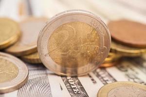 moedas de euro sobre notas de dólar foto