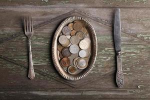 pequena placa de metal texturizada com moedas de euro e talheres na foto