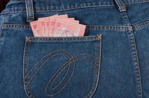 notas da malásia no bolso da calça jeans foto