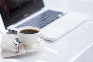 xícara de café e laptop para negócios foto