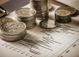 moedas e gráfico em tom sépia foto