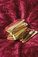 barras de ouro em veludo vermelho foto