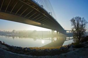 nascer do sol enevoado em uma margem do rio sob a ponte de cabo foto