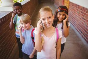 crianças da escola usando telefones celulares no corredor da escola foto
