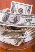 notas de dólar na tigela de vidro foto